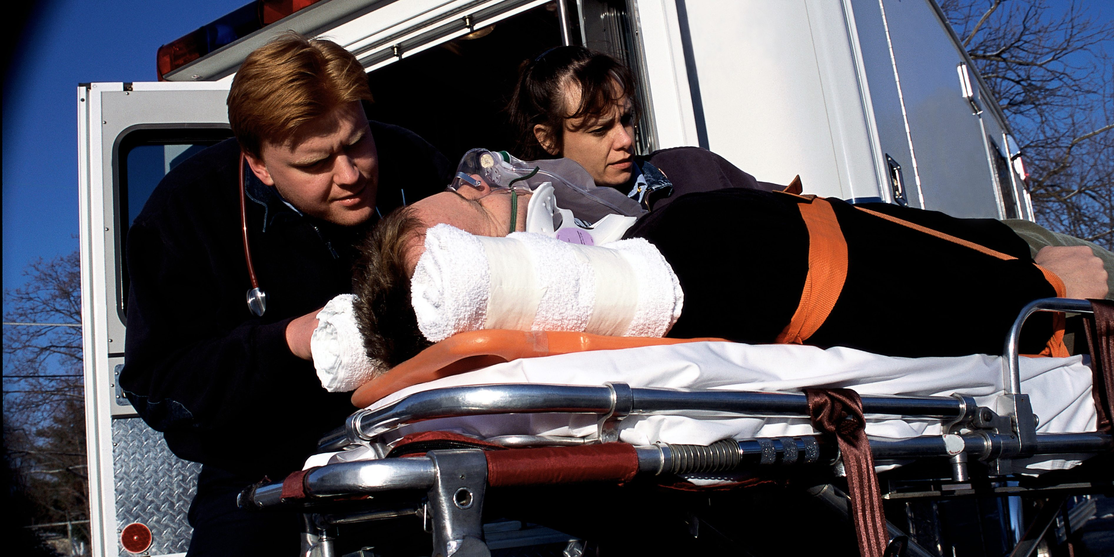 Two Caucasian paramedics, one male and one female, strapping an injured Caucasian male into a stretcher